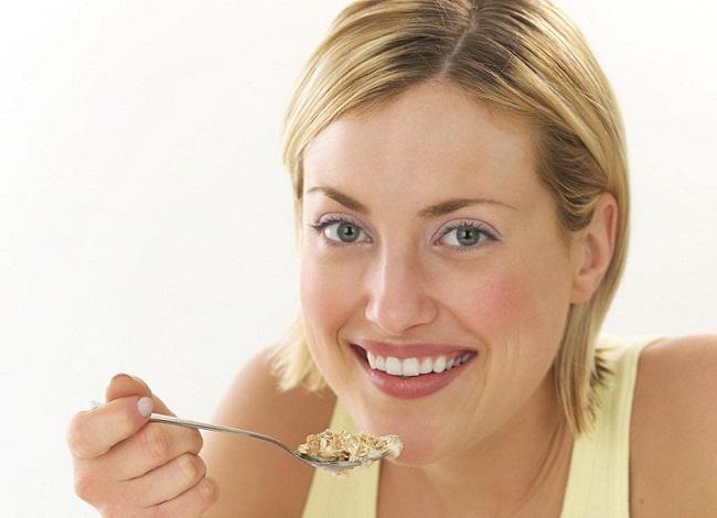 Девушка ест кашу