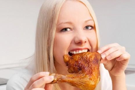 Девушка ест курицу