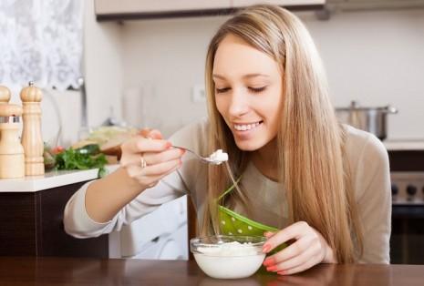 Девушка ест творог