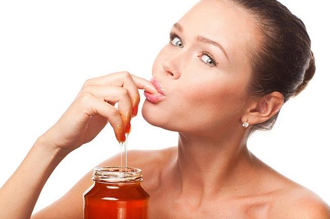 Девушка ест мед